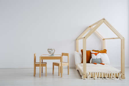 Cozy room for kids with a comfortable, wooden bed, and a small table