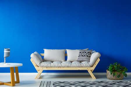 植物、小さなテーブル、およびシンプルなスタイルのリビング ルームでモダンなソファ 写真素材