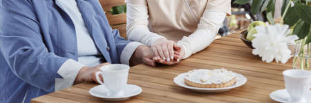 Concept of supporting aging people, nurse holding senior womans hand
