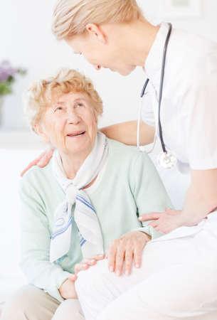 年配の女性と話している彼女のアシスタントに白の制服のリビング ルームに座っています。