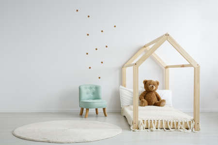 Elegant mint chair in a spacious, decorated kid's bedroom standing next to a modern wooden bed with a teddy bear sitting on it Фото со стока