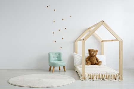 Elegante muntstoel in een ruime, versierde kinderkamer naast een modern houten bed met een teddybeer erop Stockfoto