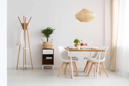 Eenvoudige modieuze Skandinavische eetkamer in minimalistisch wit appartement