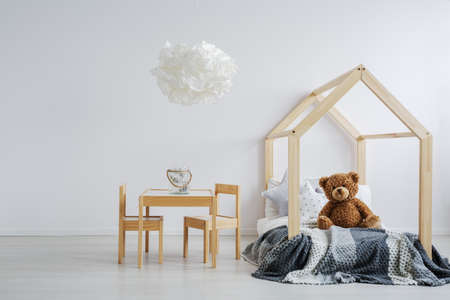Modern kids room with a teddy bear sitting on a stylish, wooden bed next to a small table with a jar on it