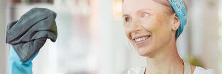 Glimlachende vrouw die een zwarte doek in haar hand houdt en het gebruikt om een venster schoon te maken
