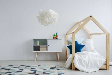 Elegant scandi style kids room with a modern, wooden bed next to a cupboard with two cacti standing on it