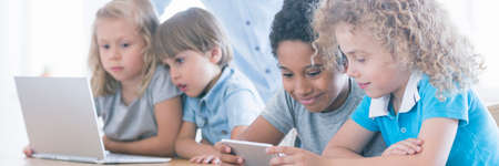 Children using laptop and smartphone during classes in modern primary school