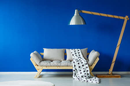 white wood floor: Stylish living room with furniture such as large lamp hanging over a comfortable couch with a spotty blanket on it, and a circular carpet on the floor Stock Photo