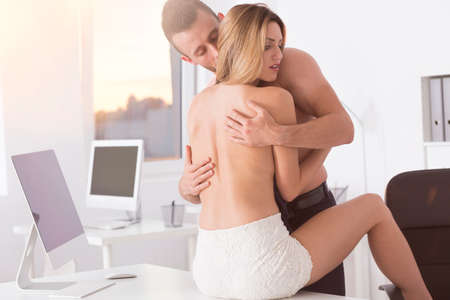 Young couple having passionate sex in the office photo