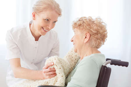 Smiling caregiver gives a beige blanket to pensioner on wheelchair sick on osteoporosis Stock Photo