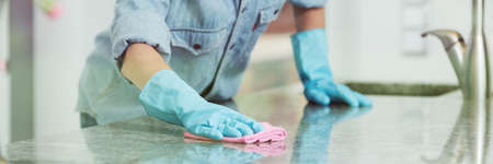 Woman in jean shirt, and rubber gloves cleaning a kitchen countertop with a pink dishrag