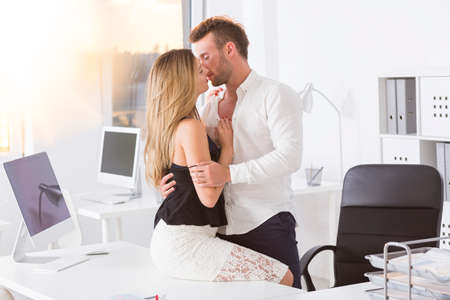 Attractive man kissing a woman at work photo