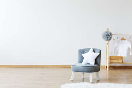 Star shaped pillow on a grey chic chair in a minimalist design scandinavian room Imagens