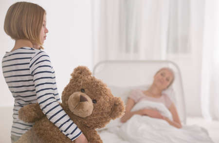 Little girl visiting her seriously ill mother lying in hospital bed Stock Photo