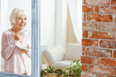 Happy elder lady with a tea cup standing by the window
