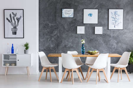 Five simple paintings on concrete dark wall in minimalist dining room with designed chairs