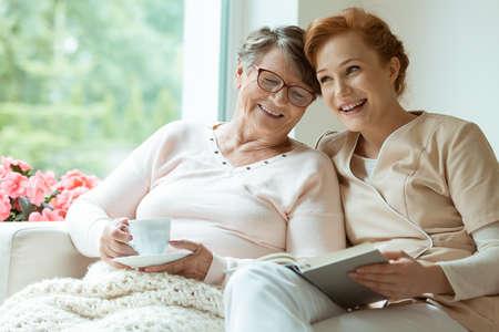 할머니의 요양원에서 간호사로 자원 봉사하는 백인 손녀 스톡 콘텐츠