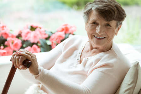 Elder lady sitting on the couch with wooden walking stick and smiling