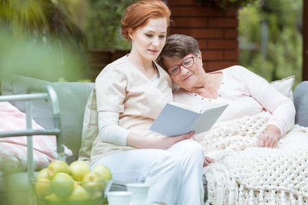 Elder lady in glasses covered with blanket resting her head on nurse's shoulder Standard-Bild