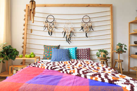 Big bed with ethnic ethereal multicolor decorations