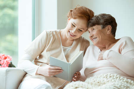Two ladies sitting on the couch and reading a book in hospice room