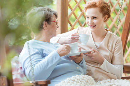 Senior pensioner in glasses sitting outside and drinking tea together with hospice worker Stock Photo
