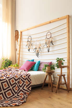 Wooden bedhead with dreamcatchers above the bed with ethnic decorations Stock Photo