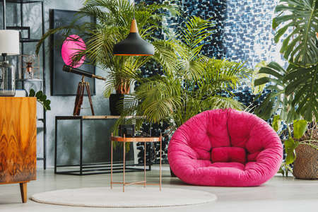 Spacious living room with pink plush armchair, telescope and exotic plants