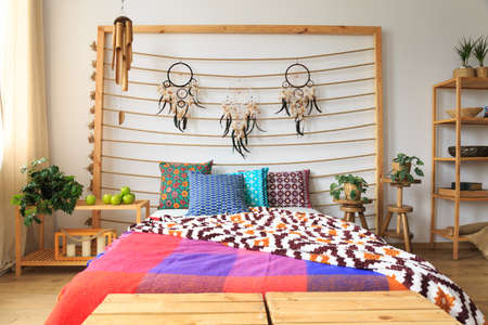 Ethnic ethereal bedroom with colorful bed sheets Stock Photo