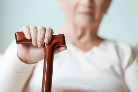 Sad older lady's hand placed on wooden walking stick Stockfoto