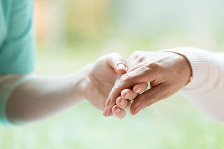 Hand of nurse holding elder womans palm, blurred background Stock Photo
