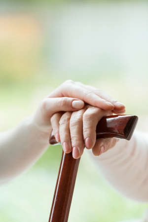 Young caregiver's hand placed on elder's hand holding walking stick
