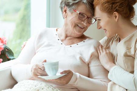 Oudere vrouw met een kopje thee en haar vriendelijke verzorger die in elkaar kijkt