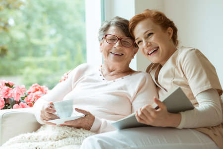 Happy grandma with glasses holding cup of coffee and laughing with her granddaughter volunteering as caretaker Stock Photo