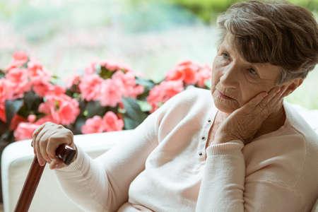 Une dame âgée triste assise sur le canapé et s'inquiète de sa santé Banque d'images - 84422293