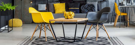 Modern black and yellow living room with citrus on table in apartment