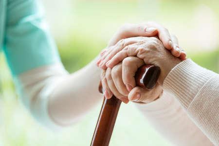 Enfermera en delantal consolando a una anciana tocando sus manos Foto de archivo - 84494208
