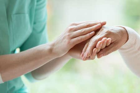 Jeune gardien massage la main du retraité avec la maladie de Parkinson Banque d'images - 84423445