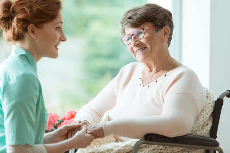 Young caucasian nurse supporting elder woman with glasses in wheelchair Stock Photo