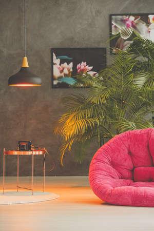 Vintage kamer met een licht op een salontafel en een roze fauteuil
