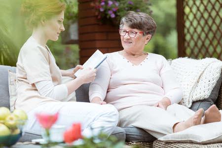 庭のソファーに座りながらアルツハイマー病と女性の個人的なジャーナルを読んで若い介護者 写真素材