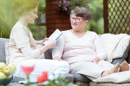 Giovane caregiver leggere giornale personale di signora con malattia di Alzheimer mentre seduto sul divano da giardino Archivio Fotografico - 84496113