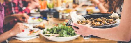 Sirviendo a amigos con patatas asadas en una bandeja negra