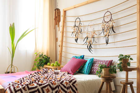 Big bed with wooden bedhead with dreamcatchers on the rope