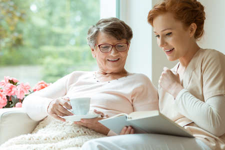 Smiling elder lady with blanket and glasses listening to her nurse reading a book during free time