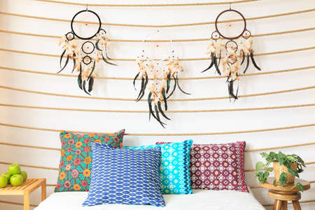 Three dreamcatchers above the bed with decorative cushions Stock Photo