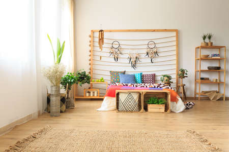 Ethnic ethereal bedroom with colorful bed and a wicker rug and wooden shelves