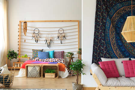 Colorful ethnic bedroom with dreamcatcher decoration on the bedhead Stock Photo