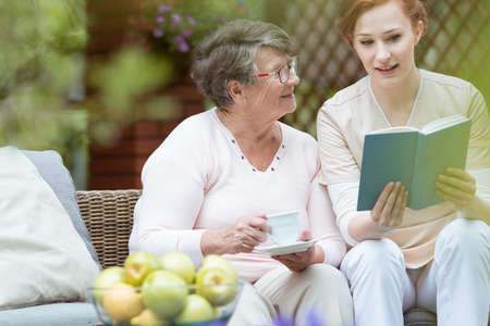 Young nurse reading a book to pensioner with glasses in the garden