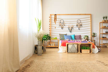 Ethnic ethereal bedroom with multicolor bed and a wattle rug Stock Photo
